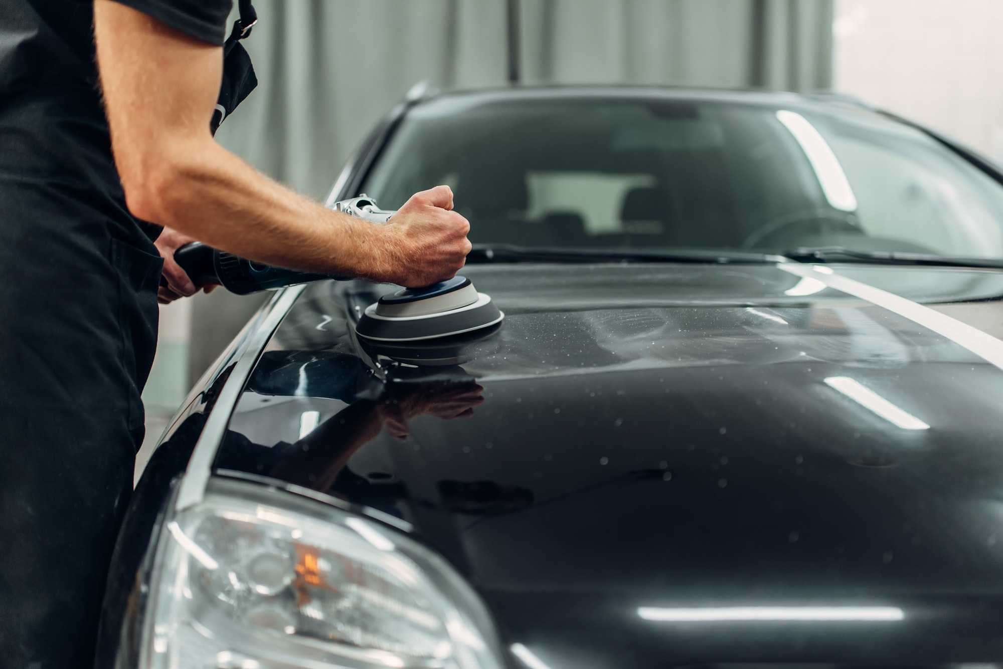 Male person with polishing machine cleans car
